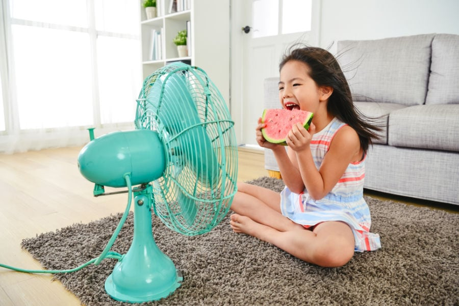 Little girl sitting in front of a fan eating watermelon because the air conditioner needs repair.