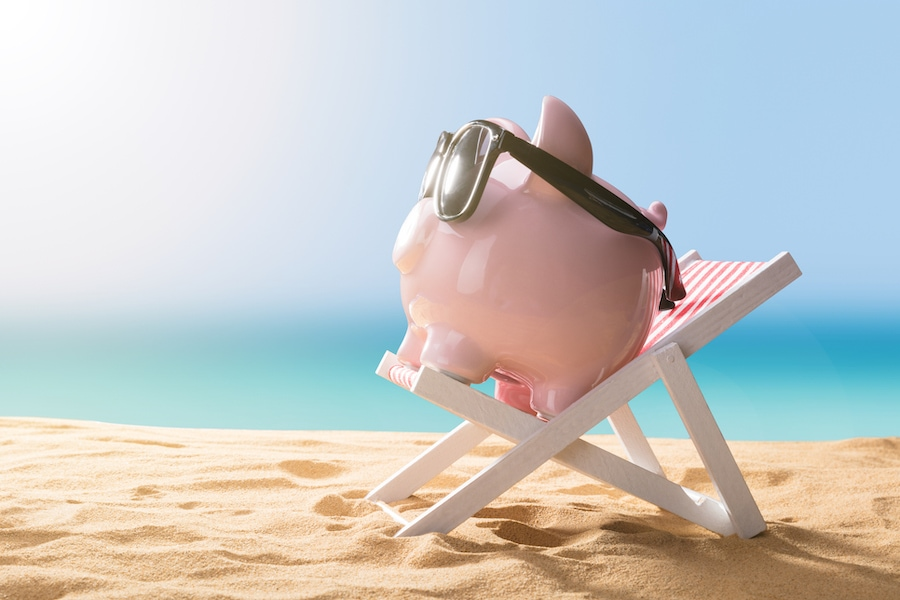 Close-up Of A Pink Piggy Bank Wearing Sunglasses Relaxing On Deck Chair.