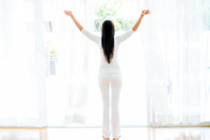 Woman opening the windows at home and enjoying some fresh air